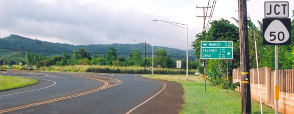 East end of state route 540 at junction with state route 50, with sign indicating in both miles and kilometers distances to Waimea to the left, and Kalaheo and Lihue to the right