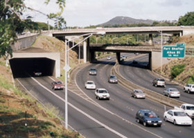 Two eastbound lanes of H-1 emerge from Middle Street Tunnel, merge with three eastbound lanes of Moanalua Freeway