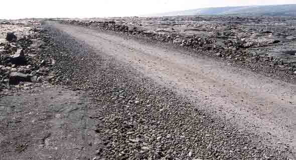 One-lane gravel road through field of pahoehoe lava