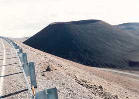 Large black cinder cone alongside road