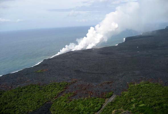 Overhead view from northeast  of new west end of access road, showing solidified lava covering part of last unpaved segment; steam plumes indicate where lava is flowing into the ocean