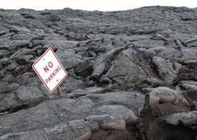 'No parking' sign sticking out of solidified lava