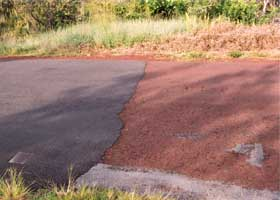 Closeup of transition from old red to new black pavement, with new pavement on left