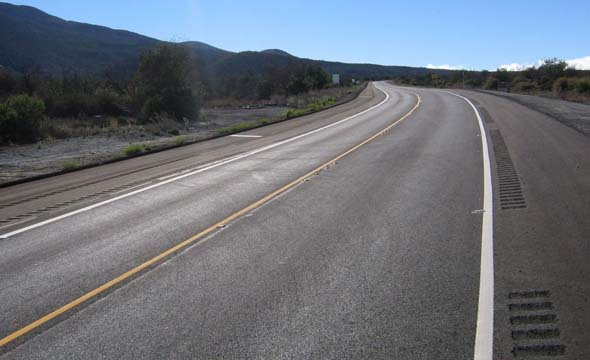 New Ala Mauna Saddle Road alignment facing eastbound, with reflectors embedded in the road and rumble strips on the shoulders