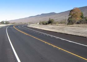 More smooth pavement at the west end of the new alignment, with right turn lane to the turnoff for Mauna Kea State Park