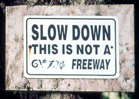 Unofficial sign on dirt road: 'Slow Down, This Is Not A @\#%! Freeway'