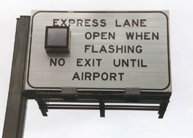 "Overhead:  ""Express Lane Open When Flashing, No Exit Until Airport"""